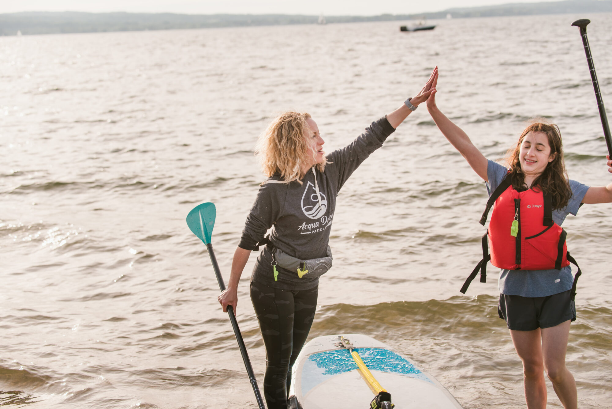 Acqua Dolce Paddle Holli and Student high five during SUP lesson
