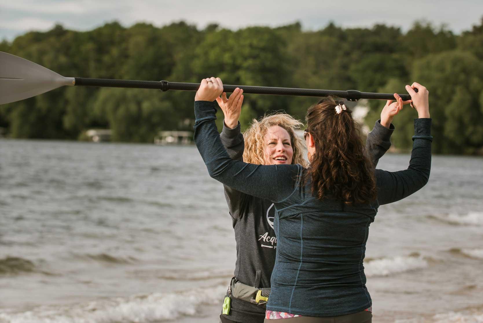 Acqua Dolce Paddle Holli instructing student holding paddle above head